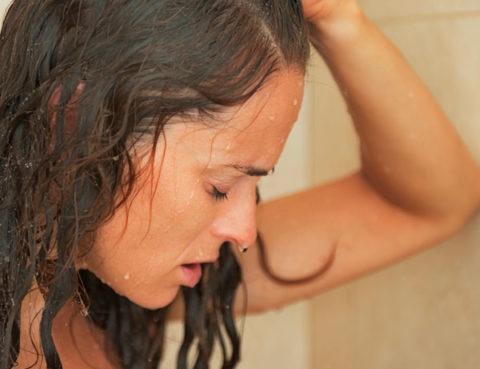 mulher na ducha com dor